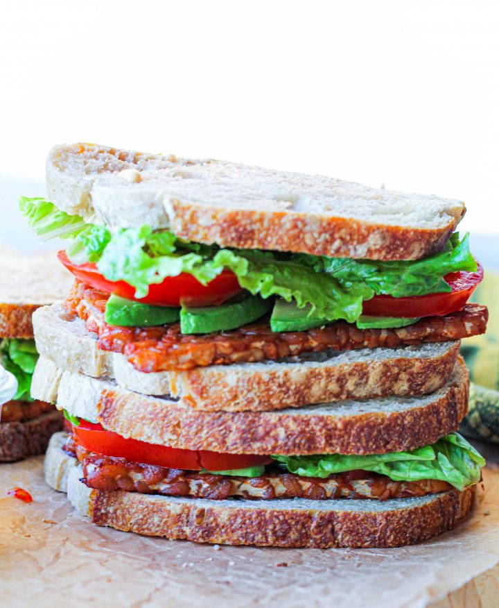 a straight on shot of two stacked tempeh blt sandwiches on a paper-lined wooden board