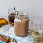 straight on shot of the dirty chai smoothie in a glass surrounded by a jar of hemp, coffee, ripe banana, and cinnamon sticks.
