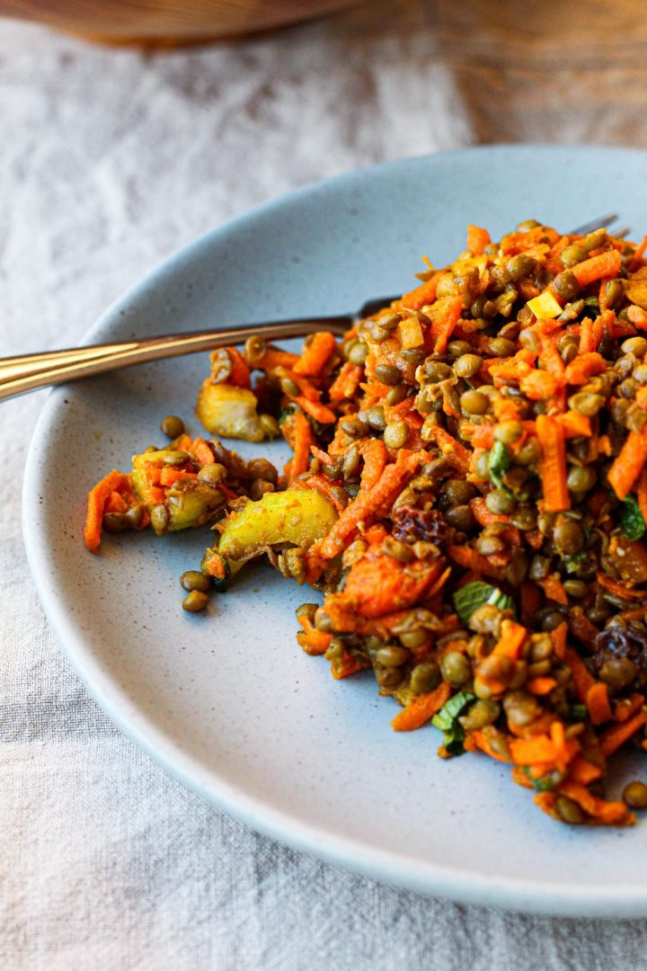 straight on shot of the moroccan lentil carrot salad on a blue plate