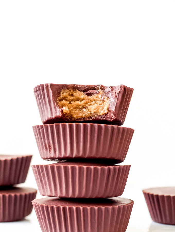 a straight on shot of a stack of four chocolate hazelnut butter cups against a white backdrop