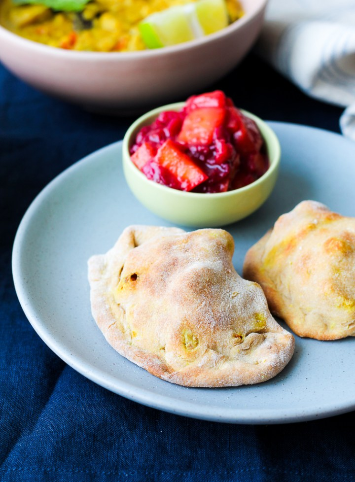 a straight on shot of two samosas on a blue plate with a small dish of the cranberry mango chutney beside them