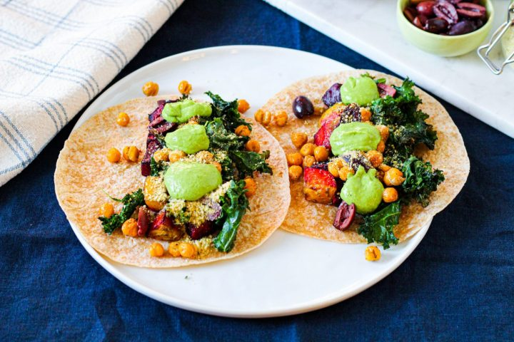 straight on shot of two tacos on a white plate on a navy blue backdrop