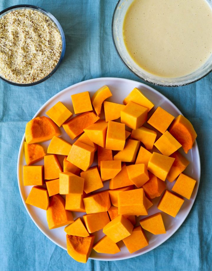 overhead shot of the squash cubes on a plate with a dish of nut parmesan and a dish of chickpea flour batter beside it