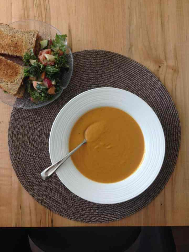 overhead shot of lunch, a bowl of sweet potato white bean soup, a sandwich, and salad