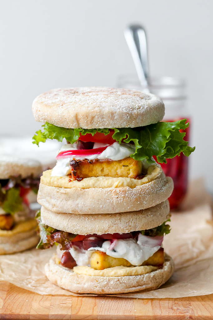straight on image of the greek tofu sandwiches stacked on top of each other on a wooden board
