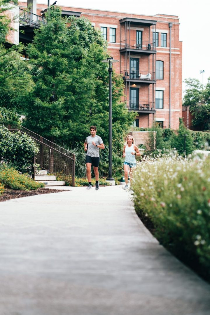 a man and a woman running on a city sidewalk