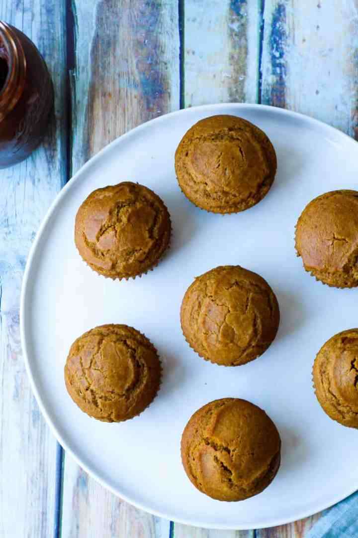 overhead shot of pumpkin cupcakes on a white plate against a blue and brown wood backdrop