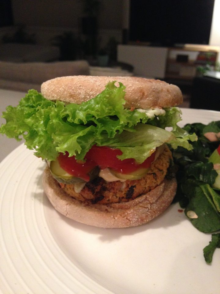 a sun-dried tomato chickpea burger in a bun with pickles, lettuce, and tomato