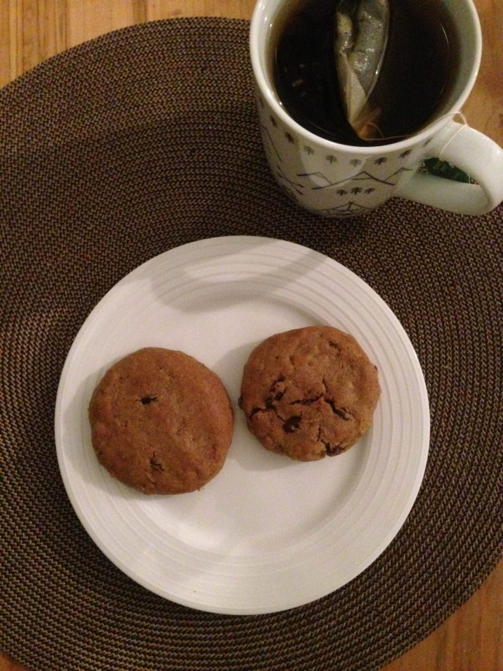 overhead shot of two oatmeal raisin cookies on a plate and a cup of tea
