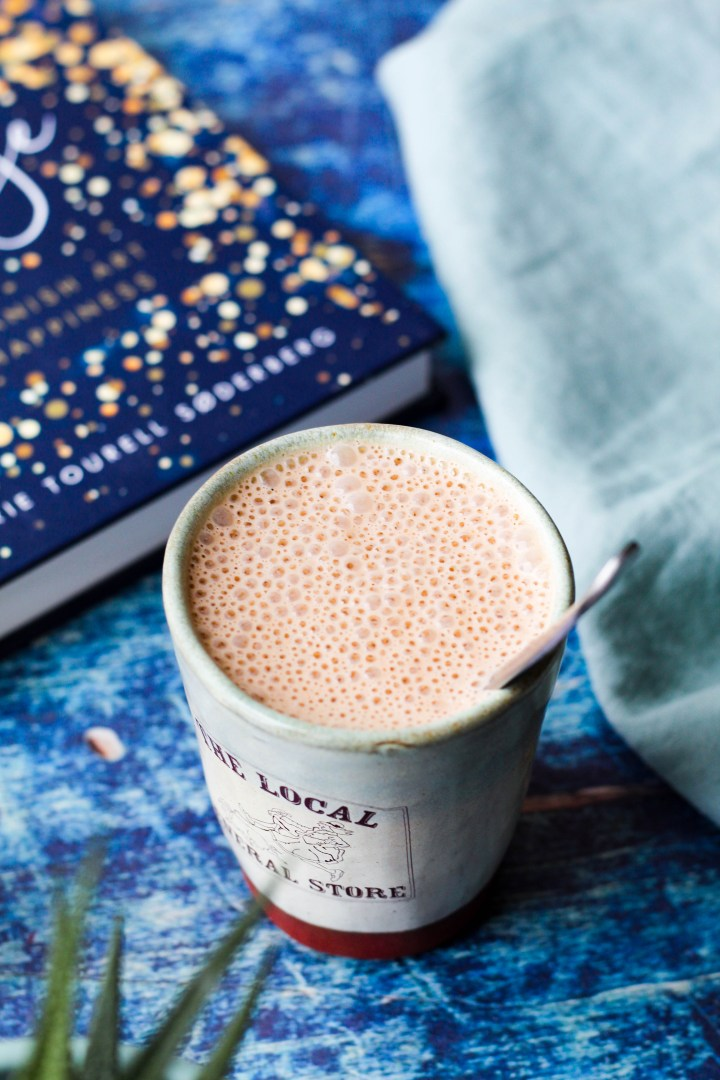 an angled shot of a mug of the hot chocolate on a blue rustic backdrop