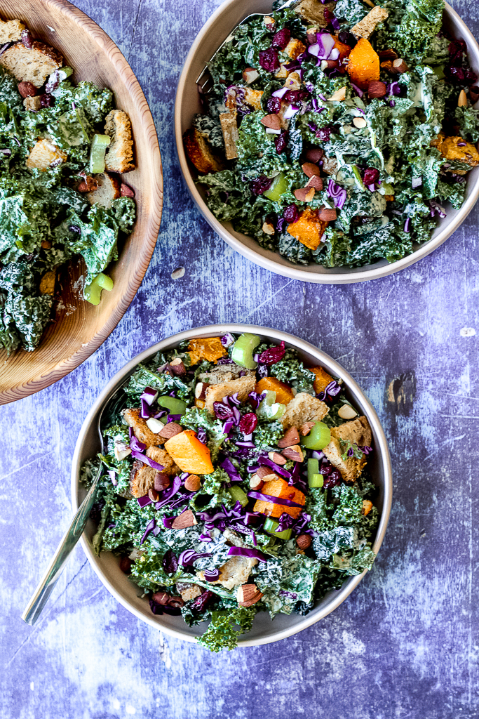 overhead shot of the kale Caesar salad in two serving bowls on a blue backdrop