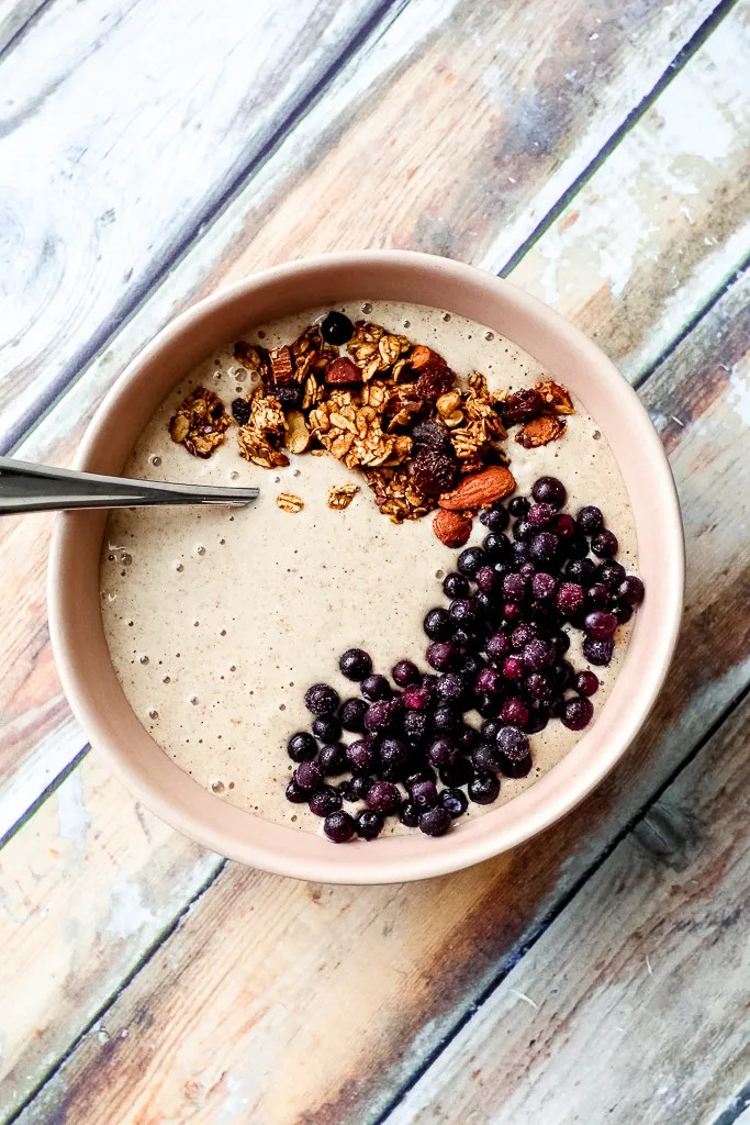 overhead shot of the fully dressed eggnog smoothie bowl topped with granola and frozen blueberries on a wooden backdrop