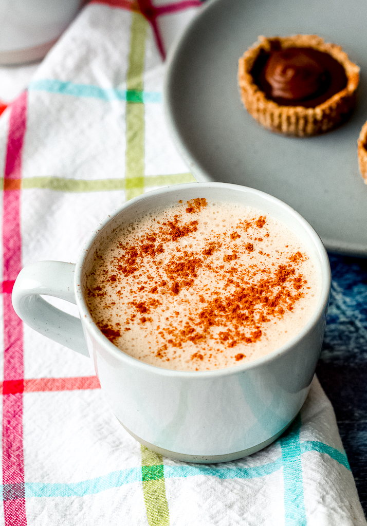 straight on shot of the vegan eggnog latte on a colourful towel against a blue background