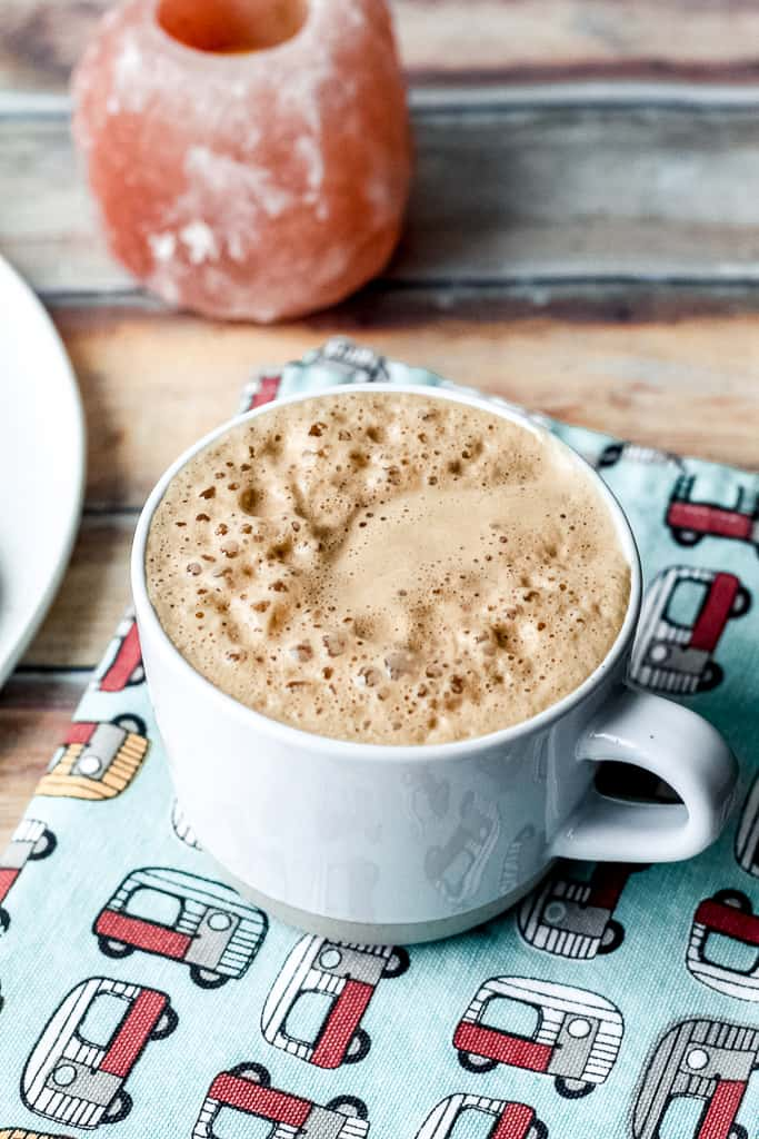 straight on shot of a gingerbread latte in a light blue mug on a decorative towel