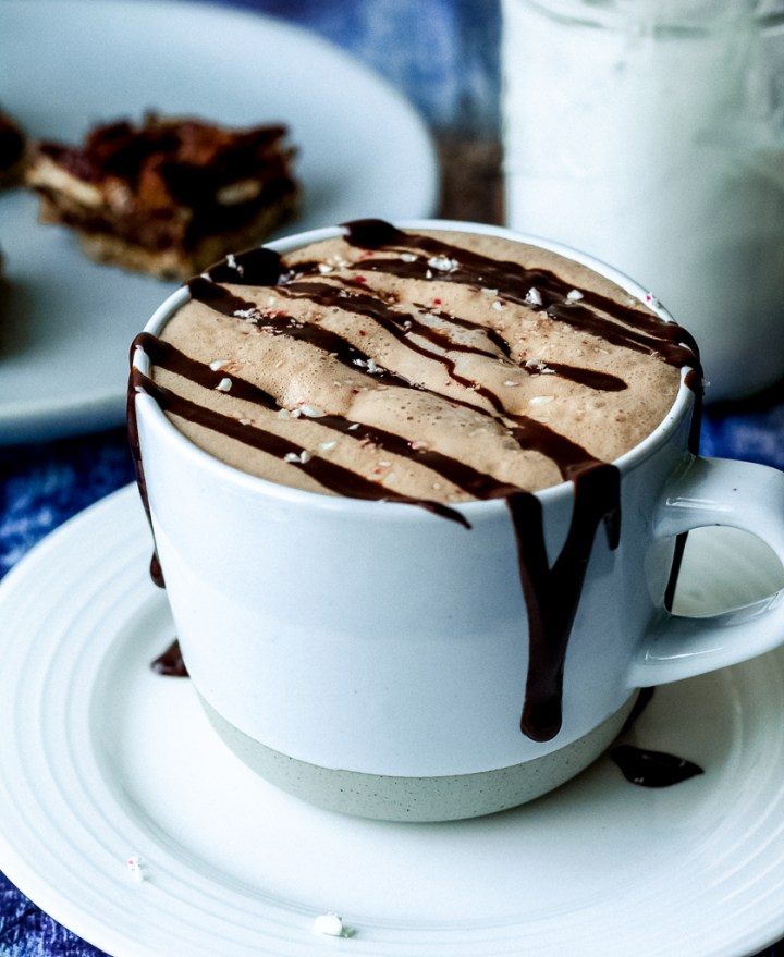 a straight on shot of a mug of peppermint mocha with chocolate sauce drizzled over top on a white plate with candy canes crushed on top