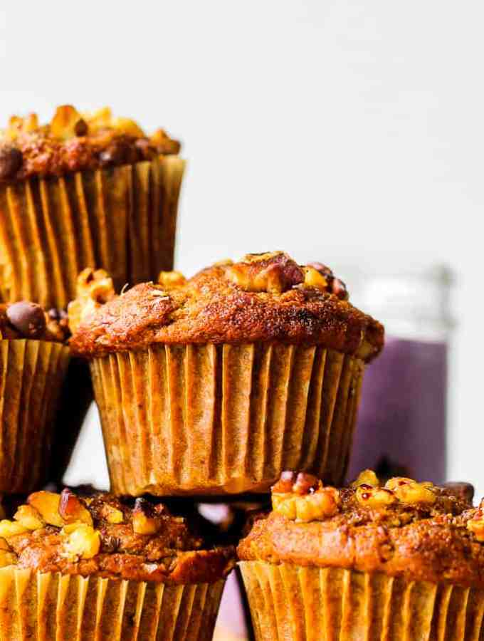 a stack of the muffins with a blueberry smoothie in the background