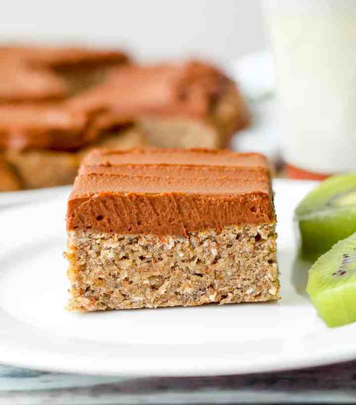 a straight on shot of one banana oatmeal almond breakfast bar on a white plate