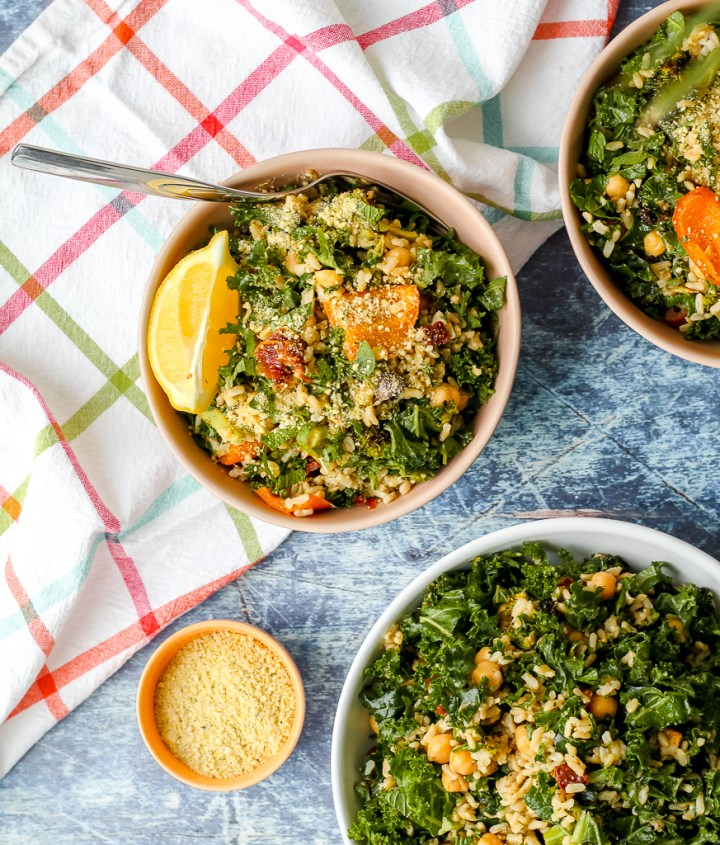 overhead photo of two bowls of salad and a big serving bowl of brown rice broccoli chickpea salad on a blue backdrop
