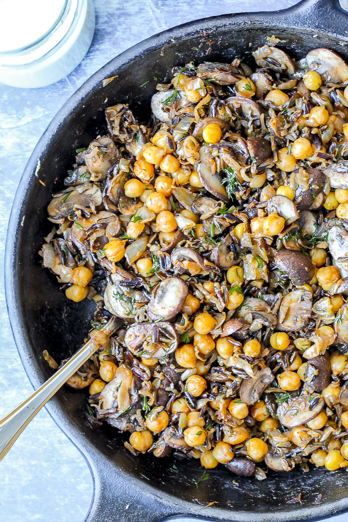 an overhead shot of the chickpeas, wild rice, and mushrooms mix in a cast iron skillet