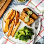an overhead shot of two slices of chickpea meatloaf on a white plate with oven fries and steamed broccoli