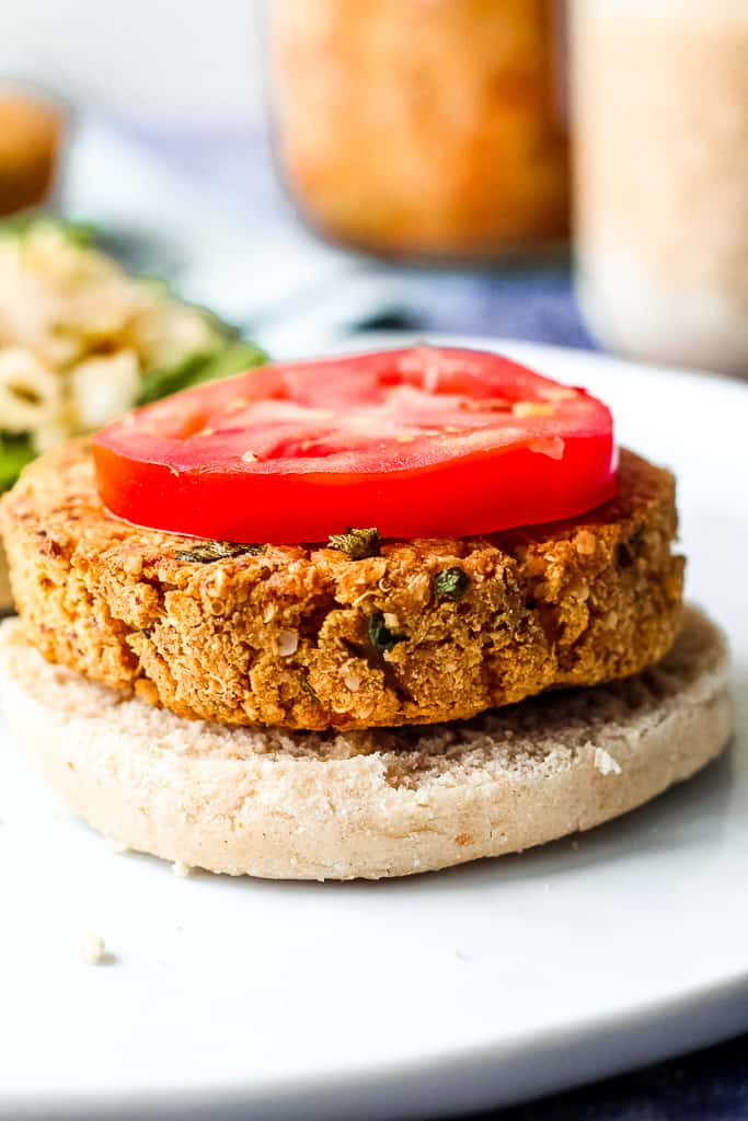straight on shot of a spicy tofu burger on a bun with a slice of tomato on top