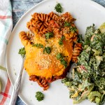 an overhead shot of the lentil mushroom pasta bake on a plate with a side of kale Caesar salad