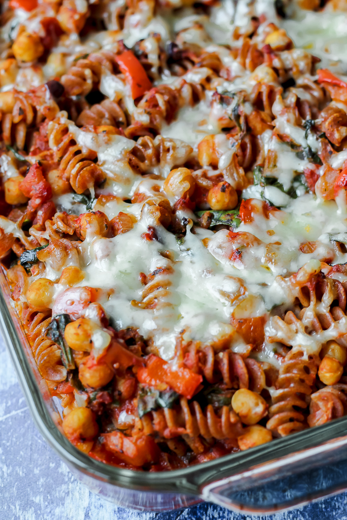 straight on close up shot of chickpea pasta bake on a blue backdrop