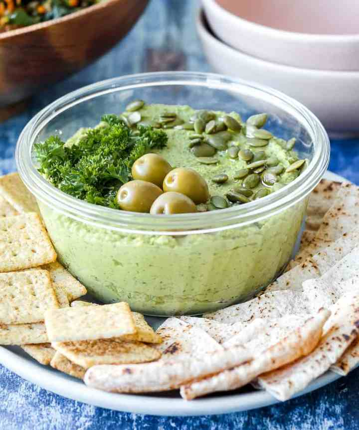 a straight on shot of a container of the green goddess hummus surrounded by crackers and pita
