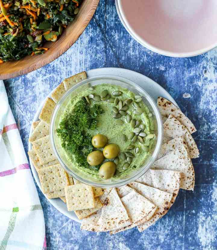 an overhead shot of the green goddess hummus in a serving dish surrounded by pita and crackers