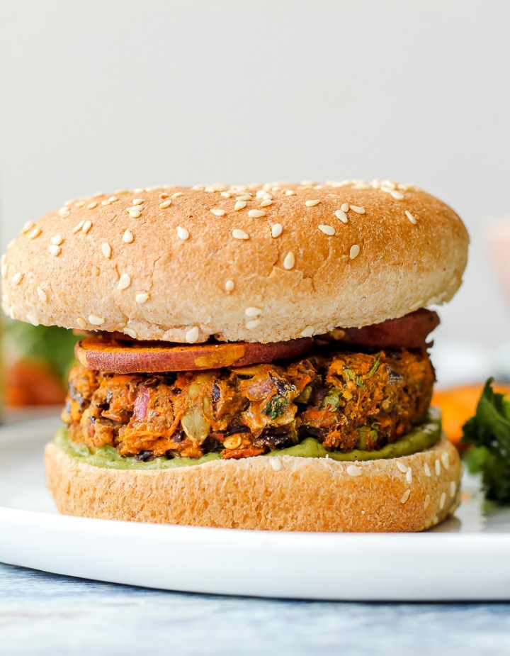 a straight on shot of one Caribbean veggie burger on a whole grain bun, on a white plate