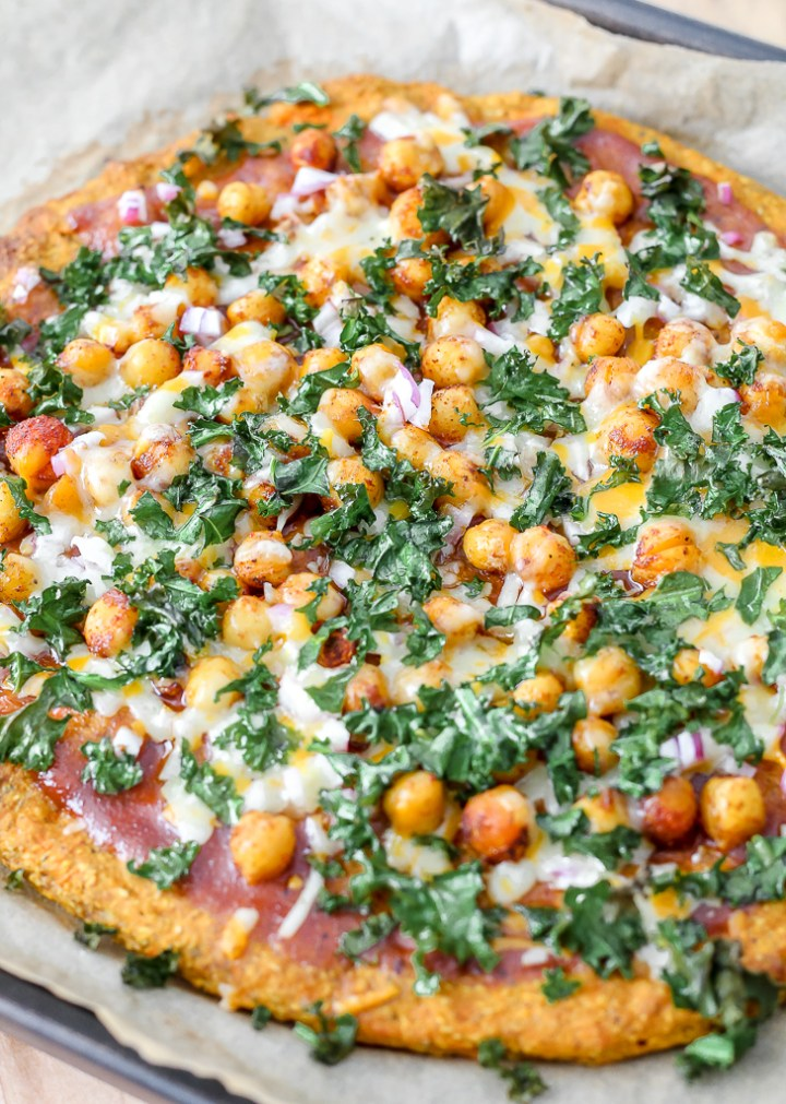 straight on shot of a whole barbecue chickpea pizza on sweet potato crust on a baking sheet