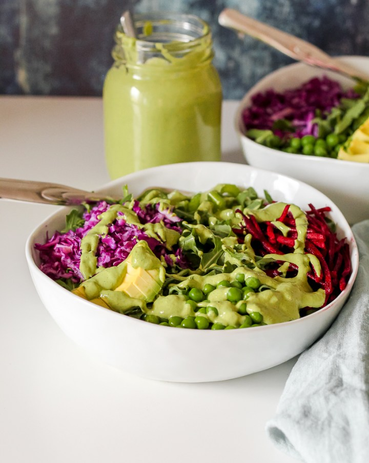 straight on shot of two bowls of the arugula, beet, pea, avocado salad on a white table with a jar of dressing on the side