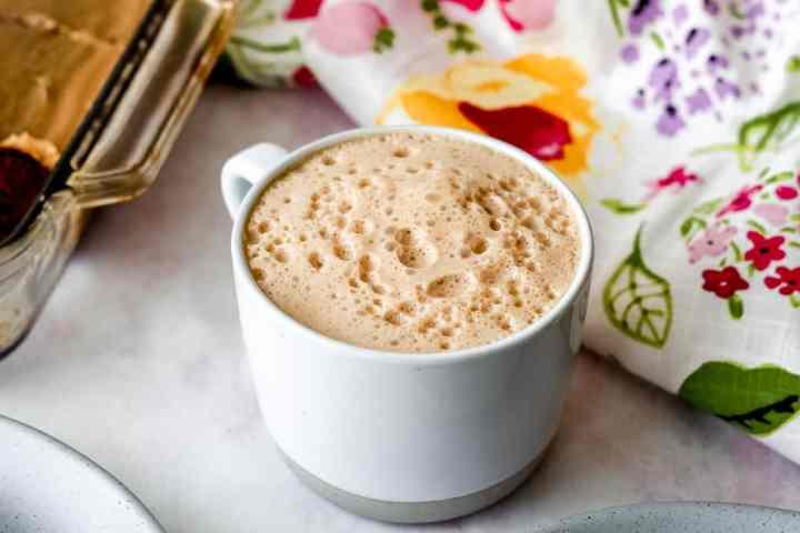 horizontal shot of white chocolate vegan snickerdoodle latte on a light pink surface