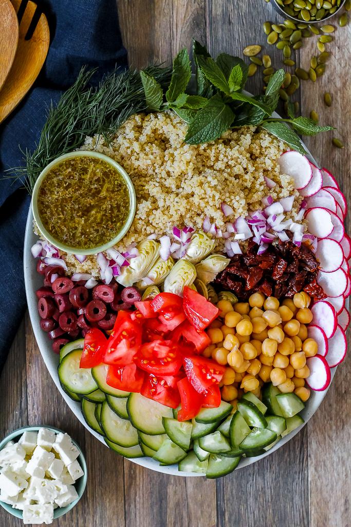overhead shot of the Greek quinoa salad components on a blue platter
