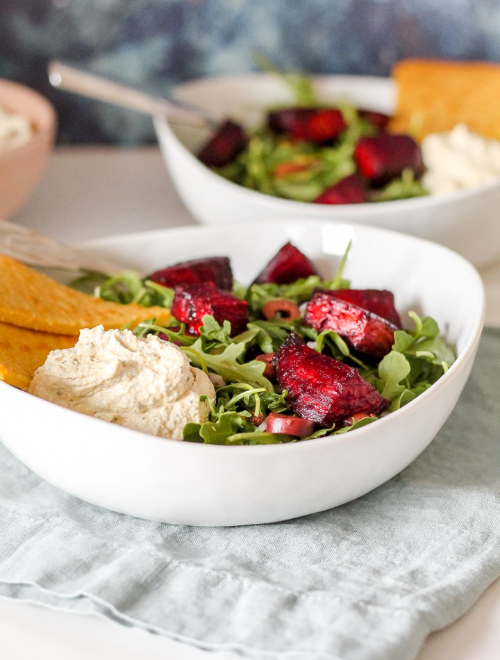 straight on shot of one of the bowls filled with arugula salad, beets, and whipped tofu