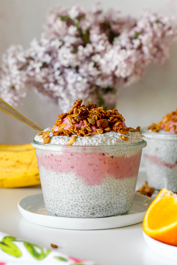 two chia pudding parfaits on a white table with a vase of lilacs and a bunch of bananas in the background
