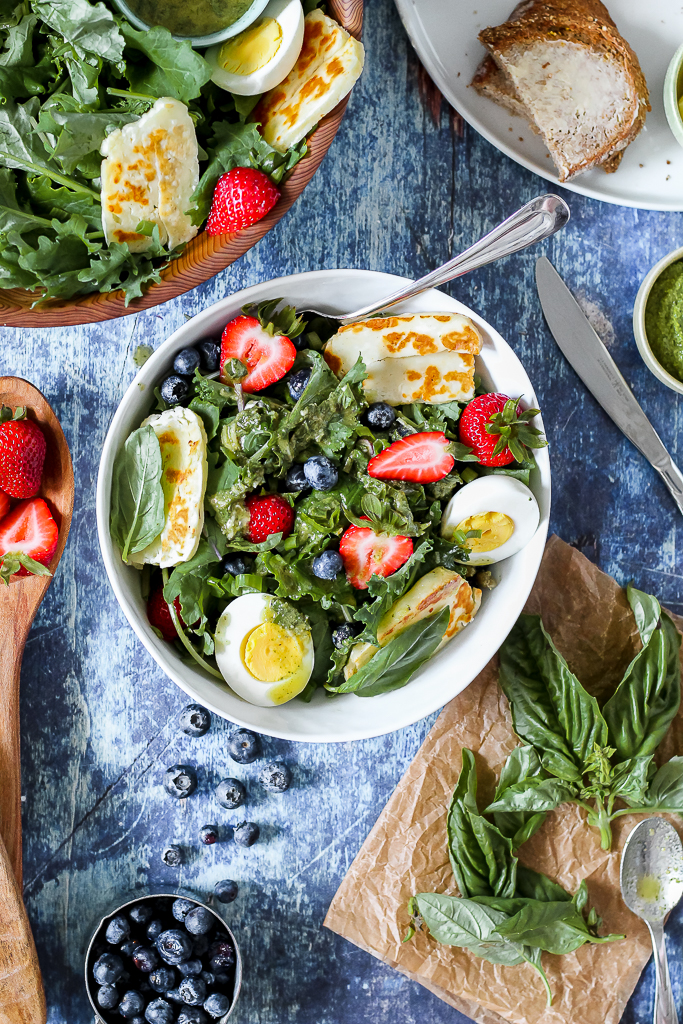 overhead shot of a serving of the salad in a white bowl on a blue backdrop with blueberries and strawberries scattered here and there.