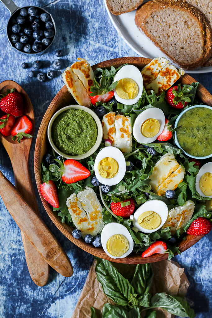 overhead shot of a big wooden bowl containing the kale, halloumi, eggs, and berries