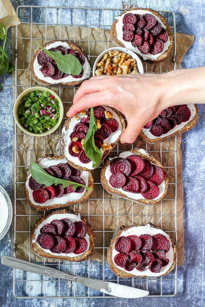 overhead shot of a hand reaching for a slice of beet goat cheese crostini with honey