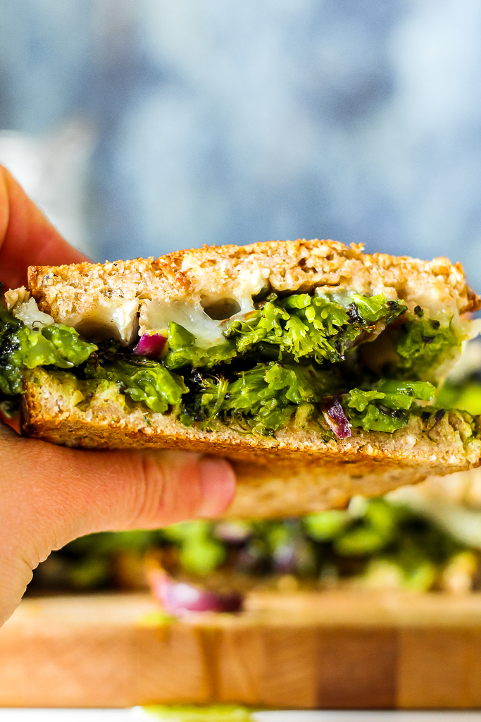 straight on shot of one of the basil pesto brie grilled cheese sandwiches being picked up by hand to be eaten