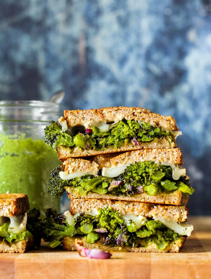straight on shot of the broccoli brie and basil pesto grilled cheese sliced in half and stacked one on top of the other on a wooden board