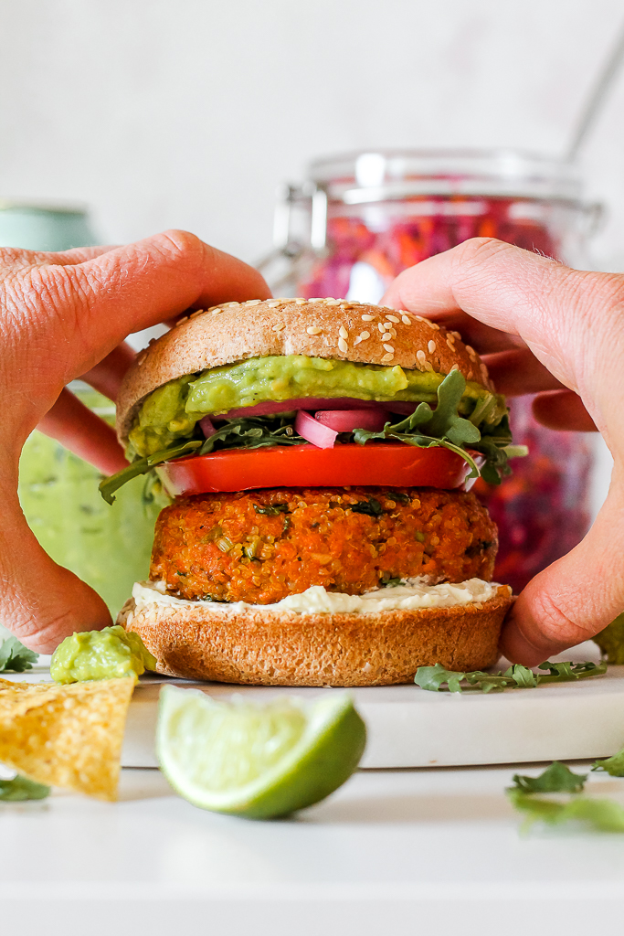 a Mexican salmon quinoa burger being picked up in someone's hands