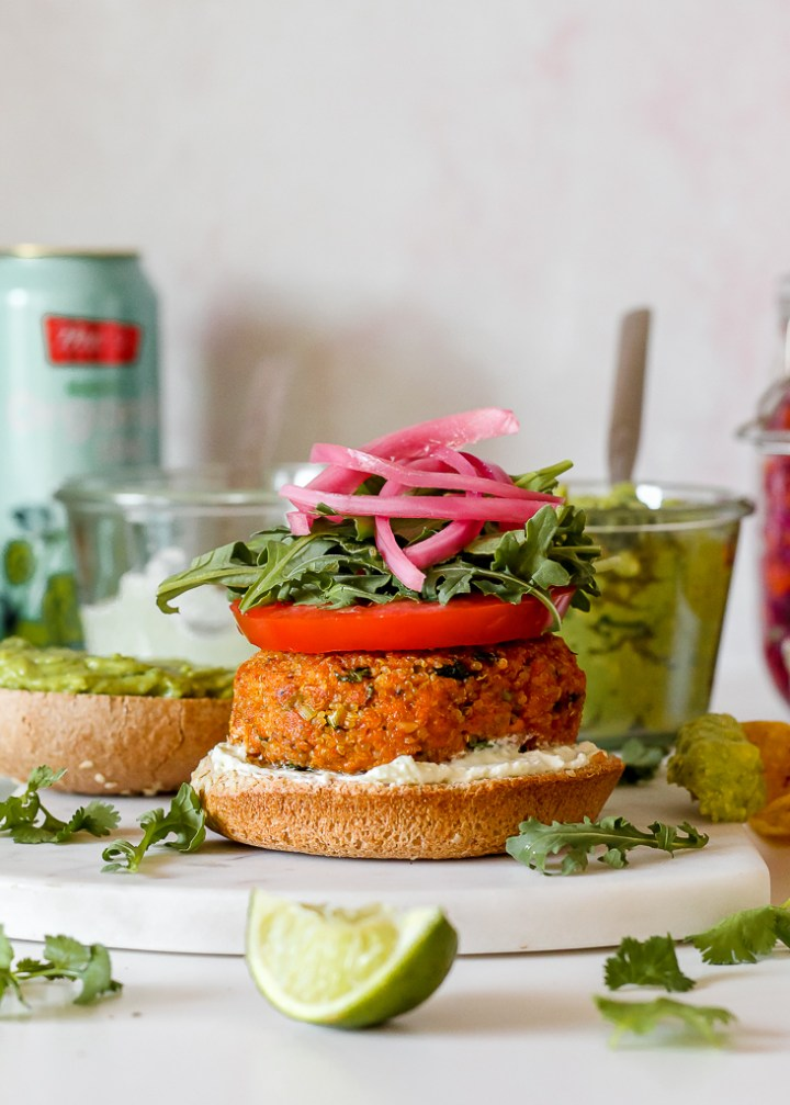 straight on shot of a Mexican salmon quinoa burger on a bun with whipped chèvre and tomato and arugula