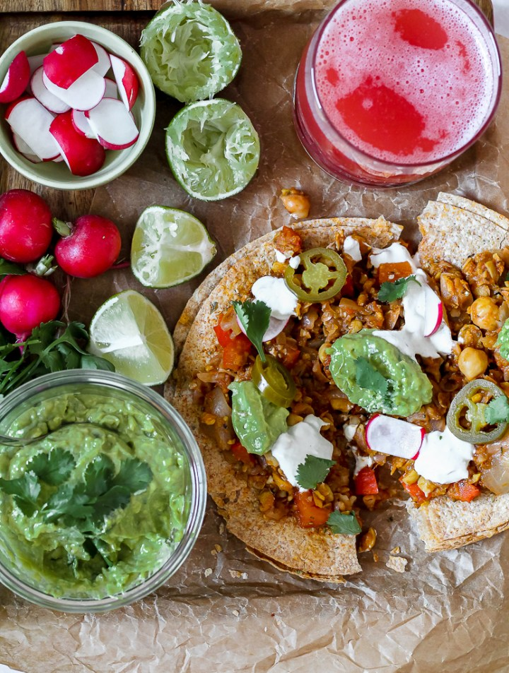 overhead shot of the tostadadilla surrounded by guacamole, lime, and radishes