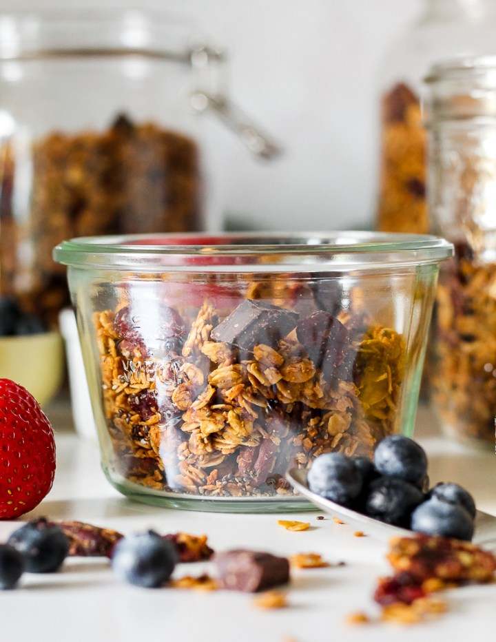 straight on shot of a dish of granola on a white table with jars of granola in the background