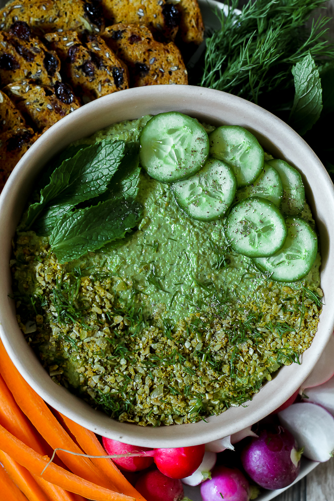 close up overhead shot of the green pea herb hummus in a pink dish