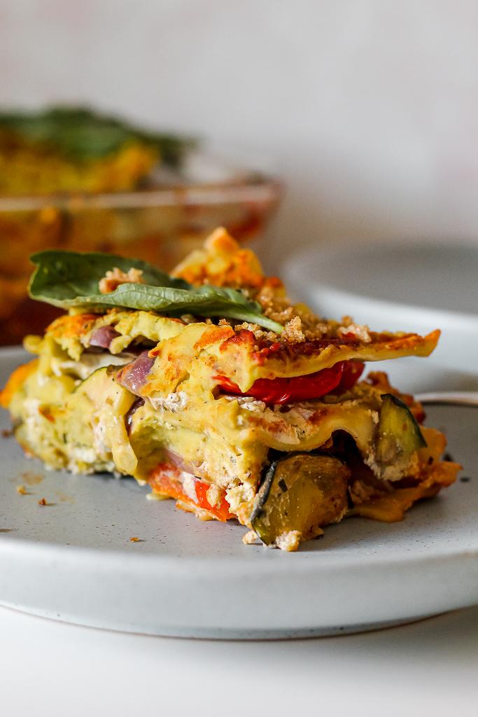 straight on shot of a slice of vegan white bean basil pesto cream lasagna on a light blue plate