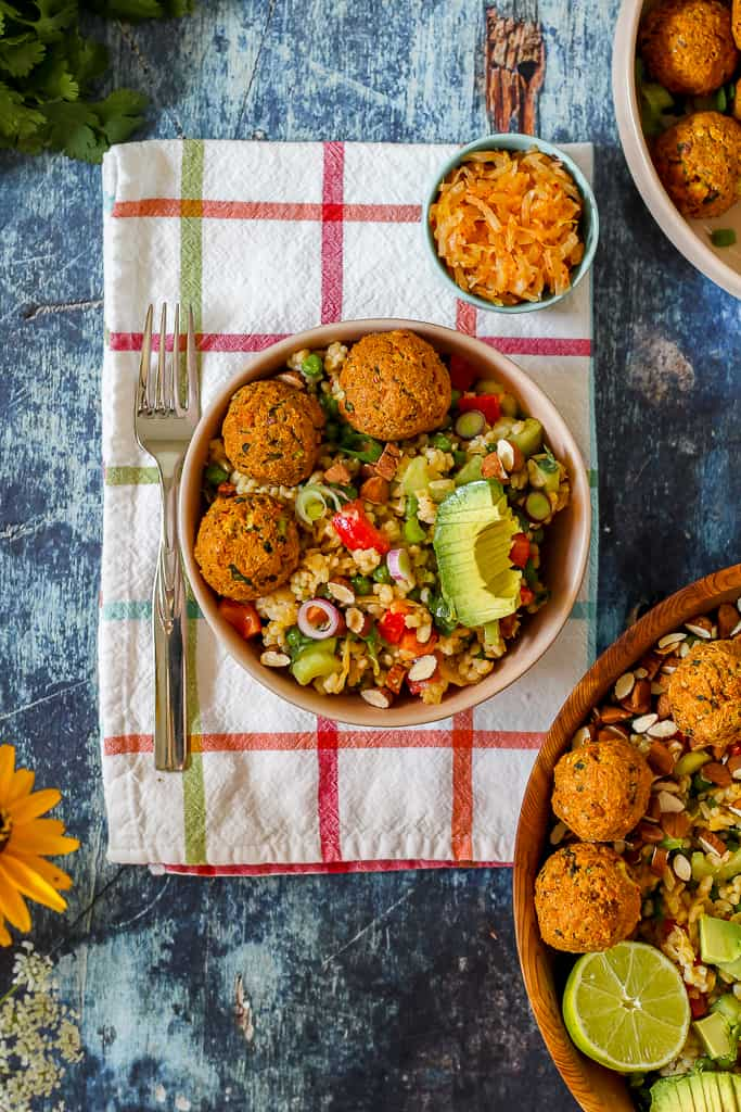 zoomed out overhead photo of the salmon balls on a bed of the kimchi brown rice salad in a pink bowl