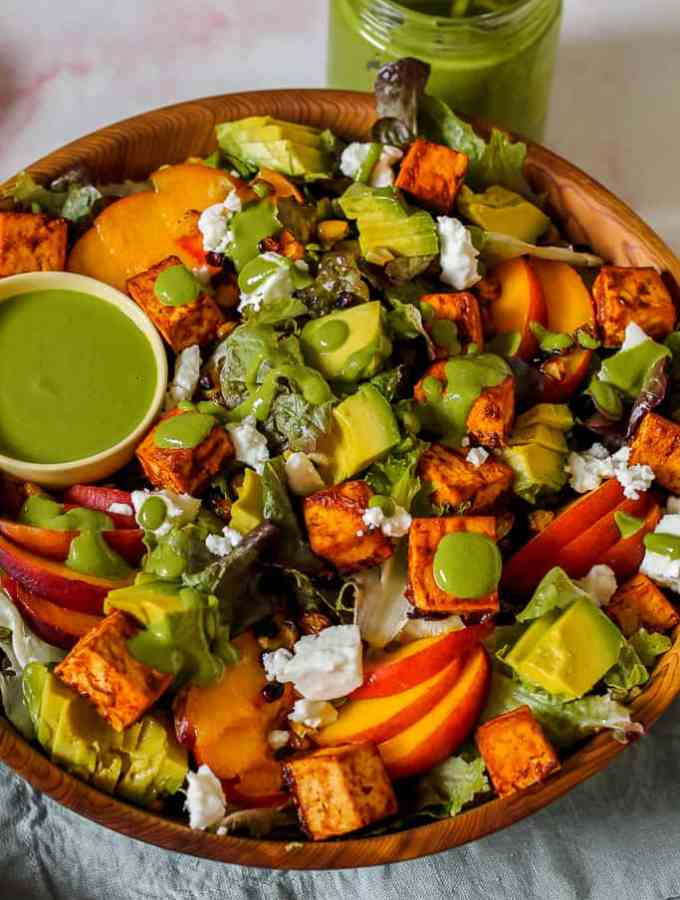 straight on shot of a big bowl of the salad topped with chipotle tofu in a wooden bowl