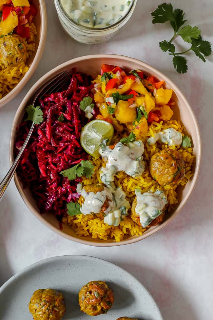 overhead photo of a masala chicken meatball bowl topped with raita